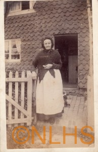 Lady outside cottage formerly on the site of the Village Club